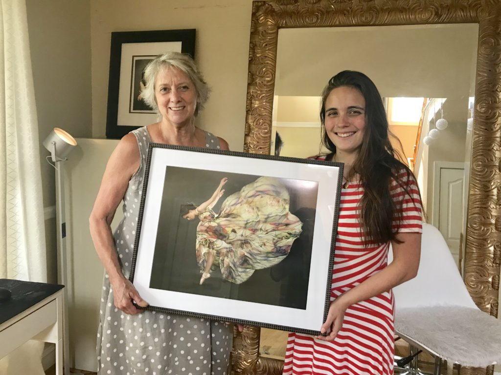 Happy ballet dancer holding her framed portrait with mother