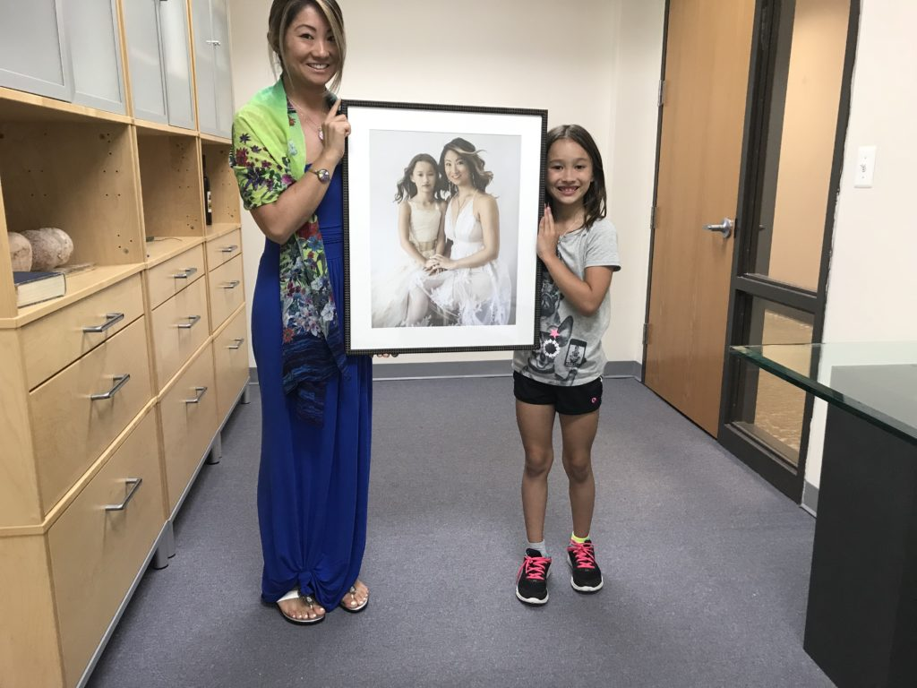An asian mother and daughter holding their portrait